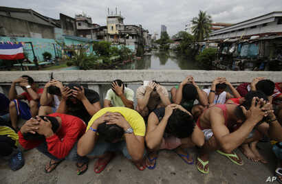"""FILE -  Filipino men place their hands over their heads as they are rounded up during a police operation as part of the continuing """"War on Drugs"""" campaign of Philippine President Rodrigo Duterte in Manila, Philippines."""