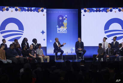 Former President Barack Obama, center left, gestures next to Golden State Warriors basketball player Stephen Curry while speaking at the My Brother's Keeper Alliance Summit in Oakland, Calif., Feb. 19, 2019.