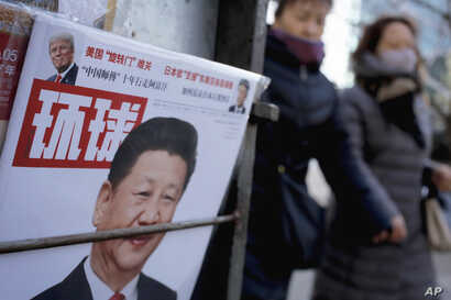 Women walk past a news stand displaying a Chinese news magazine fronting a photo of Chinese President Xi Jinping and U.S. President Donald Trump in Beijing, Feb. 9, 2017.