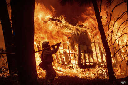 FILE - In this Nov. 9, 2018 file photo, firefighter Jose Corona sprays water as flames from the Camp Fire consume a home in Magalia, California. A massive new federal report warns that extreme weather disasters, like California's wildfires and 2018...