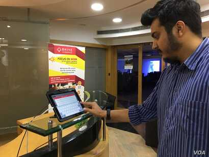 Akshay Chaturvedi, who recently began his own startup, checks into communal office space on an iPad. (E. Sarai/VOA)