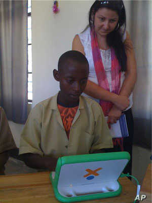A Rwandan girl uses her new OLPC laptop while an onsite specialist looks on.