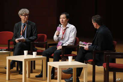 He Jiankui, a Chinese researcher, center, speaks during the Human Genome Editing Conference in Hong Kong, Wednesday, Nov. 28, 2018. He made his first public comments about his claim to have helped make the world's first gene-edited babies.