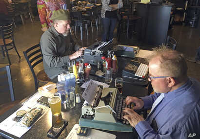 """Joe Van Cleave, left, and Rich Boucher try out various vintage typewriters at a """"type-in"""" in Albuquerque, N.M., April 23, 2017."""