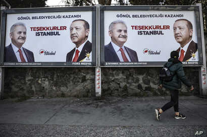 FILE - A woman walks past posters showing Binali Yildirim, left, the mayoral candidate for Istanbul of Turkey's President Recep Tayyip Erdogan's ruling Justice and Development Party's (AKP) a day after the local elections in Istanbul, April 1, 2019.