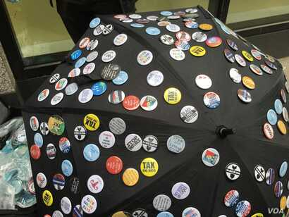 A vendor displays buttons for sale at the New York City protest march against President Donald Trump's refusal to release his tax returns, April 15, 2017.