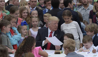 President Donald Trump shows the letter he wrote to a service member during the annual White House Easter Egg Roll on the South Lawn of the White House in Washington, April 17, 2017.