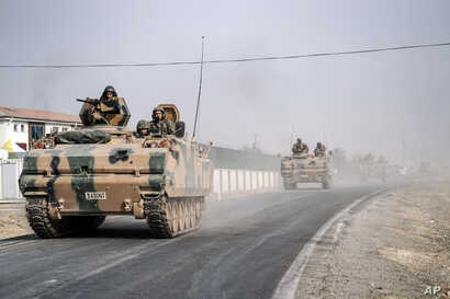 Turkish army tanks and armored personnel carriers move toward the Syrian border, in Karkamis, Turkey, Aug. 25, 2016.