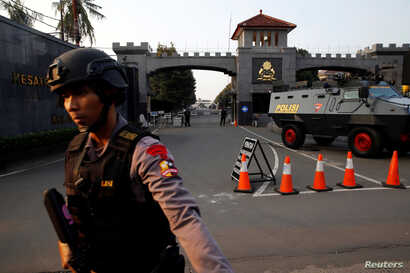 A mobile brigade policeman stands in front of the Mobile Police Brigade (Brimob) headquarters in Depok, south of Jakarta, Indonesia, May 9, 2018.
