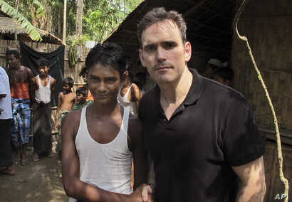American actor Matt Dillon, right, shakes hands with Noor Alam, a 17-year old Rohingya survivor of human-trafficking at Thetkabyin village, north of Sittwe in the western state of Rakhine, Myanmar, May 29, 2015.