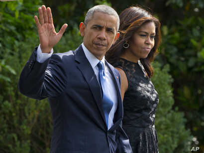 President Barack Obama and first lady Michelle Obama walk across the South Lawn of the White House in Washington, July 12, 2016, to board Marine One for a short trip to  Andrews Air Force Base, Md., before traveling to Dallas.