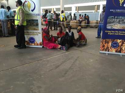 Some Zimbabwean farmers, hunngry and tired, sat on the floor in frustration as the new tobacco electronic auctioning system went down on its first day, in Harare, March, 2017. (S. Mhofu/VOA)