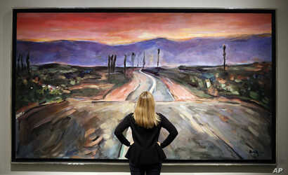 """A woman looks towards a painting by Bob Dylan called """"Endless Highway"""" on display at the exhibition called Bob Dylan The Beaten Path, at the Halcyon Gallery in London, Nov. 1, 2016."""