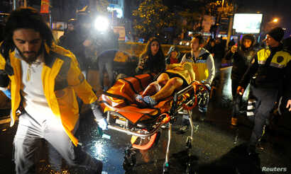 An injured woman is carried to an ambulance from a nightclub where a gun attack took place during a New Year's party in Istanbul, Turkey, Jan. 1, 2017.