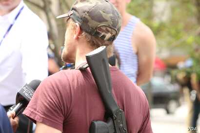 Jesse Gonzalez of Lakewood, Ohio, who carried his rifle with him, speaks to the media after arriving near the Republican National Convention in downtown Cleveland, July 18, 2016.