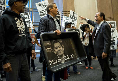 FILE - AIDS activists and others, some carrying an image of Turing Pharmaceuticals CEO Martin Shkreli in a makeshift cat litter pan, are asked to leave during a protest highlighting pharmaceutical drug pricing, in New York, Oct. 1, 2015.