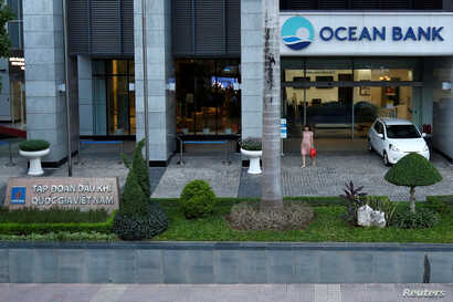 A woman walks out of a branch of Ocean Bank located in the PetroVietnam building in Hanoi, Vietnam, Sept. 1, 2017.