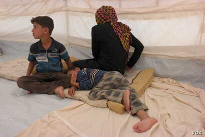 """Mohammed (9, sitting up) told us: """"My feet were very painful and tired afer having to run all night"""".  Ishwaq, her husband and their three children (all under the age of 12) managed to escape Fallujah on Monday 23 May 2016. They only managed to bring..."""