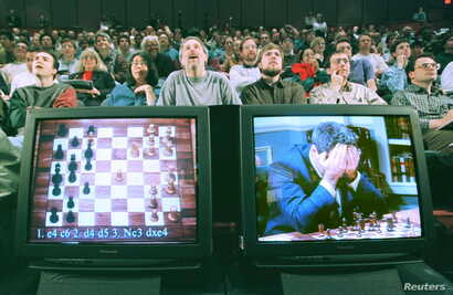 FILE - World chess champion Garry Kasparov rests his head in his hands as he is seen on a monitor during game six of the chess match against IBM supercomputer Deep Blue, May 11, 1997..