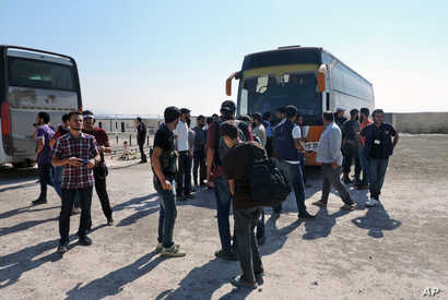 Rebels and their families arrive from the Damascus suburb of Daraya following a forced evacuation deal struck with the Syrian government that ends a grueling bombing campaign and four-year siege, in Babiska, Idlib province, Aug. 27, 2016.