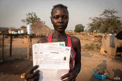 Grace Gaba holds her brother's refugee registration card in a camp for South Sudanese refugees in Aba, Democratic Republic of Congo. (J. Patinkin for VOA)