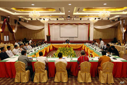 Myanmar Suu Kyi Ceasefire: FILE - A representative of an armed ethnic group, right, speaks during the second day session of a ceasefire monitoring meeting while Myanmar's de facto leader Aung San Suu Kyi, top center, listens to him Wednesday, April 2...