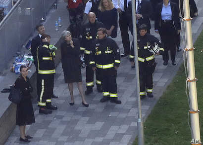 Britain's Prime Minister Theresa May, center, speaks to firefighters after arriving at Grenfield Tower in London,  June 15, 2017, following a deadly fire in the apartment block.