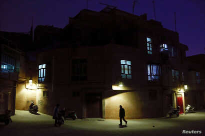 "A man walks along a street at night in the old town of Kashgar, Xinjiang Uighur Autonomous Region, China, March 23, 2017.  Thousands of ""convenience police stations"" have been built across Xinjiang. They are typically just hundreds of meters apart in..."