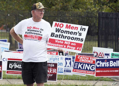 """FILE - A man urges people to vote against the Houston Equal Rights Ordinance outside an early voting center in Houston, Oct. 21, 2015. Voters rejected the bill when opponents campaigned on a message of """"No men in women's bathrooms."""""""