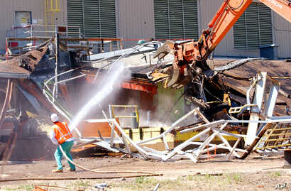 A worker sprays water to keep down the dust as a giant claw on an excavator rips apart Building 771 at the former Rocky Flats nuclear weapons plant near Golden, Colorado, July 15, 2004.