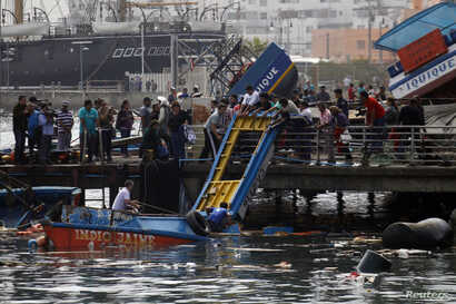 Fishermen inspect the damage caused by an earthquake and tsunami that hit the northern port of Iquique, Chile, April 2, 2014.
