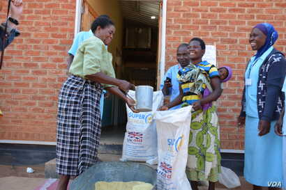 Women receive their share of 4.5 kilograms of soya flour at Mbela Health Center in Balaka distrcit, Malawi, under the WFP funded Supplementary Feeding Program.