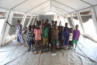 Children who fled fighting in South Sudan pose for a photograph inside a tented classroom at Bidi Bidi refugee's resettlement camp near the border with South Sudan, in northern Uganda Dec. 7, 2016.