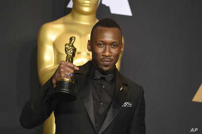 """Mahershala Ali poses in the press room with the award for best actor in a supporting role for """"Moonlight"""" at the Oscars on Feb. 26, 2017, at the Dolby Theatre in Los Angeles."""