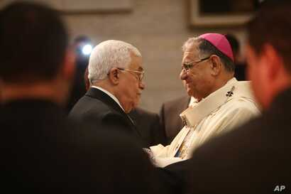 Palestinian President Mahmoud Abbas, left, greets the Latin Patriarch of Jerusalem Fouad Twal during a Christmas Midnight Mass at the Church of the Nativity in the West Bank town of Bethlehem, Dec. 25, 2015.