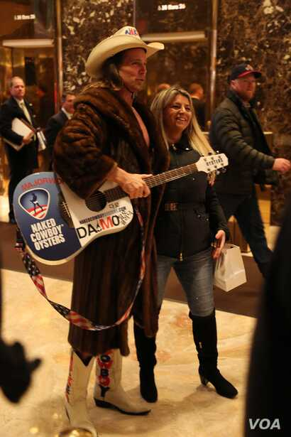 """Seemingly a Trump Tower staple, the """"naked cowboy"""" gets a lot of attention from tourists, but is mostly ignored by the press at Trump Tower in New York, Dec. 12, 2016. (R. Taylor/VOA)"""
