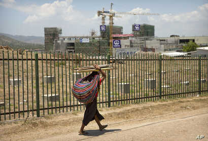 In this Nov. 14, 2018, photo, a woman carrying a bundle of sticks on her head walks past a building being built by Chinese state-owned construction firm China Railway Group Limited in Port Moresby, Papua New Guinea.