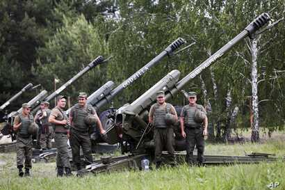 FILE - Members of a rapid reaction unit of Ukraine's National Guard stand in front of howitzers during a ceremony marking the first anniversary of its creation, in the village of Stare, 80 km east of Kyiv, Ukraine, June 2, 2016.