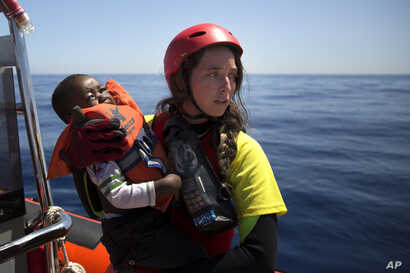 FILE - A worker of the Spanish NGO Proactiva Open Arms holds a boy rescued in the Mediterranean Sea, June 15, 2017.