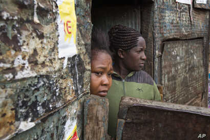 Residents watch Kenyan security forces chase supporters of Kenyan opposition leader and presidential candidate Raila Odinga who demonstrate in the Mathare area of Nairobi, Aug. 9, 2017.