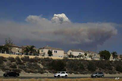 A plume of smoke from a wildfire burning near the Holy Jim area looms, Aug. 6, 2018, in Lake Forest, Calif. Authorities have evacuated cabins in two communities in the Santa Ana Mountains in Orange County because of a fast-moving wildfire.