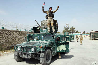 In this Oct. 2, 2015 file photo, an Afghan soldier raises his hands as a victory sign, in Kunduz city, north of Kabul, Oct. 2, 2015 after retaking the city. In October, 2016, Afghanistan forces held off an attempt by Taliban militants to take Kunduz...