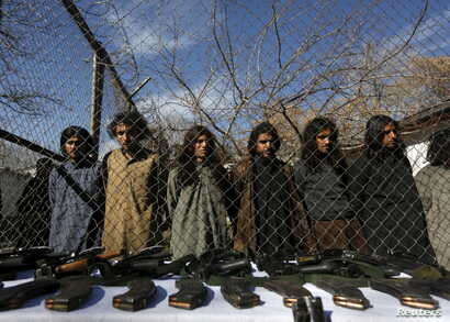 Pakistani Taliban fighters, who were arrested by Afghan border police, stand during a presentation of seized weapons and equipment to the media in Kabul, Afghanistan on January 5, 2016.