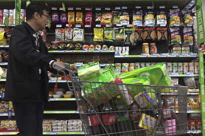 A man pushes a shopping cart past a display of nuts imported from the United States and other countries at a supermarket in Beijing, April 2, 2018.
