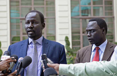 Lul Ruai Koang (L), the military spokesperson for the Sudan People's Liberation Army (SPLA) and James Gatdet Dak, spokesperson for opposition leader Riek Machar (R), give a statement to the press in Addis Ababa on May 9, 2014.