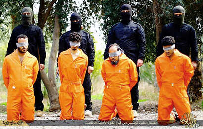 This undated image released by a militant website, which has been verified and is consistent with other AP reporting, shows members of the Islamic State group as they prepare to kill men who were allegedly spying for the U.S.-led coalition in the pro...