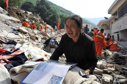 A woman cries over an album on the debris of her house at the earthquake zone of Longtoushan town, Ludian county, Zhaotong, Yunan province, China, Aug. 6, 2014.
