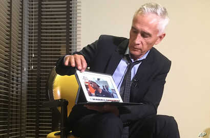Univision's Jorge Ramos shows a video he says his crew shot the previous day showing Venezuelan youth picking food scraps out of the back of a garbage truck in Caracas, during an interview at a hotel in Caracas, Venezuela, Feb. 25, 2019.