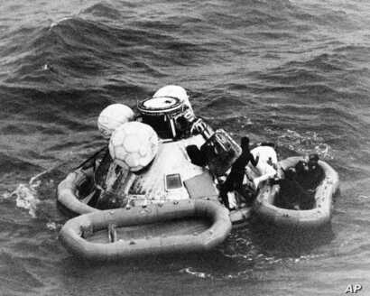FILE - Divers help recover the Apollo 8 crew from their capsule after splashdown in the Pacific Ocean, Dec. 27, 1968.