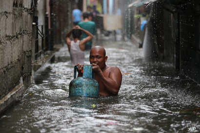 A resident carries a tank of liquified petroleum gas as he negotiates a flooded area while Typhoon Rammasun nears suburban Quezon city, Philippines, July 16, 2014.